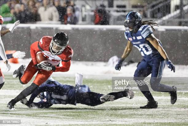 Kamar Jorden of the Calgary Stampeders falls forward leading to a fumble after a tackle by Qudarius Ford of the Toronto Argonauts as Rico Murray...