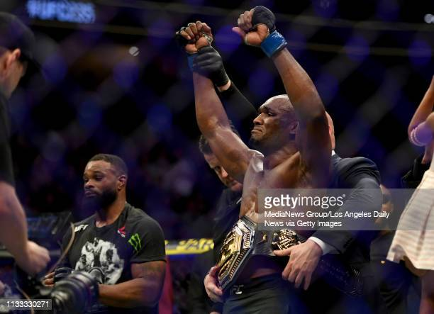 Kamaru Usman has the championship belt placed around his waist Usman defeated Tyron Woodley via judges decision to win the UFC welterweight...