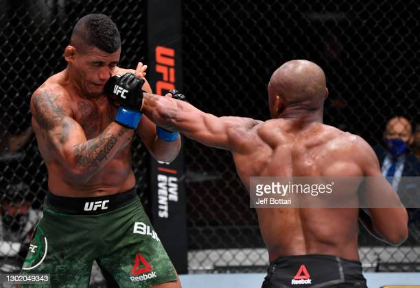 Kamaru Usman of Nigeria punches Gilbert Burns of Brazil in their UFC welterweight championship fight during the UFC 258 event at UFC APEX on February...