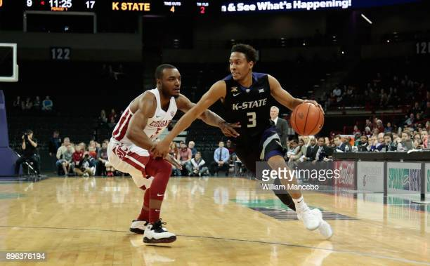 Kamau Stokes of the Kansas State Wildcats drives against Milan Acquaah of the Washington State Cougars in the first half at Spokane Veterans Memorial...