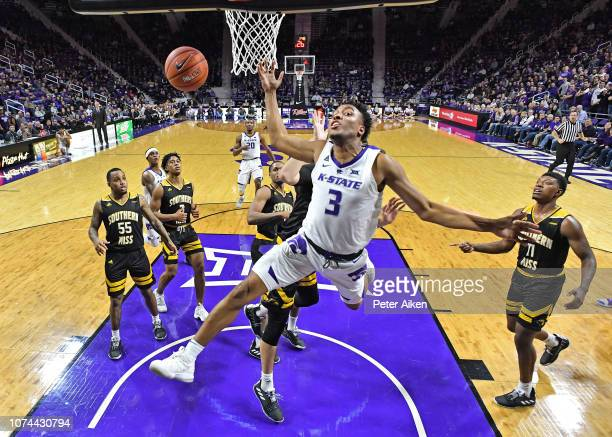 Kamau Stokes of the Kansas State Wildcats gets fouled from behind driving to the basket against the Southern Miss Golden Eagles during the first half...