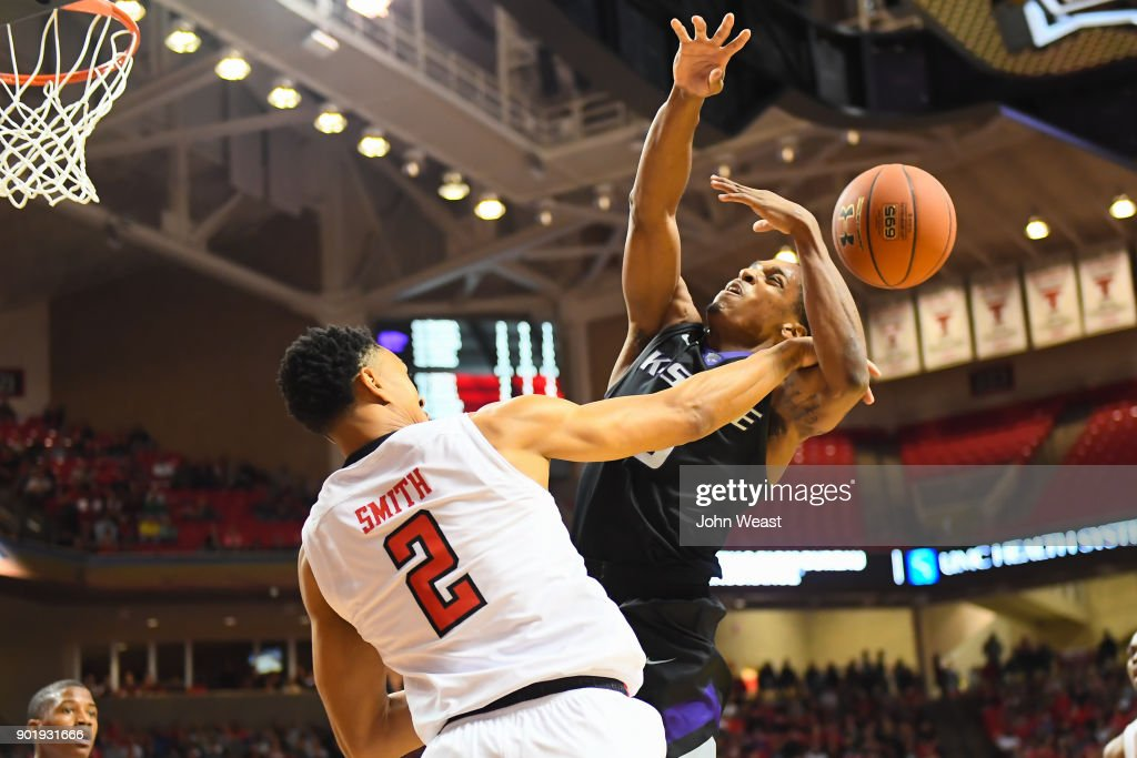 Kamau Stokes #3 of the Kansas State Wildcats goes to the basket and is fouled by Zhaire Smith #2 of the Texas Tech Red Raiders during the first half of the game on January 6, 2018 at United Supermarket Arena in Lubbock, Texas.