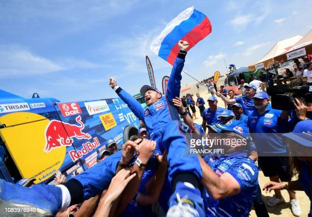 Kamaz truck Russian driver Eduard Nikolaev is congratulated by staff members after winning the Dakar Rally 2019 at the end of the last stage between...