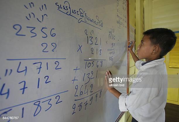 Kambodscha Tonle Sap See Schulunterricht auf einem Boot Junge an der Tafel beim Rechnen