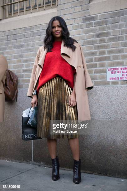 Kamie Crawford is seen attending Dion Lee during New York Fashion Week wearing a camel wool coat with red sweater and gold skirt on February 11 2017...