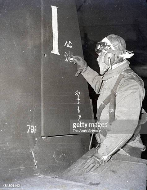 Kamikaze poliot writes a message on the tail of the aircraft before the attack at the Imperial Japanese Navy Air Force Kanoya Air Base circa May 1945...