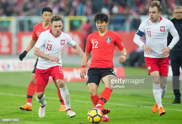 Kamil Grosicki and Maciej Rybus of Poland vie Chang-hoon Kwon during the international friendly soccer match between Poland and South Korea national...