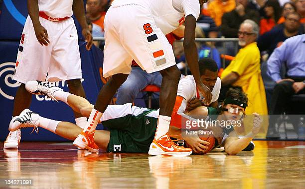 Kamil Janton of the Eastern Michigan Eagles fights for the ball on the ground with James Southerland of the Syracuse Orange during the game at the...