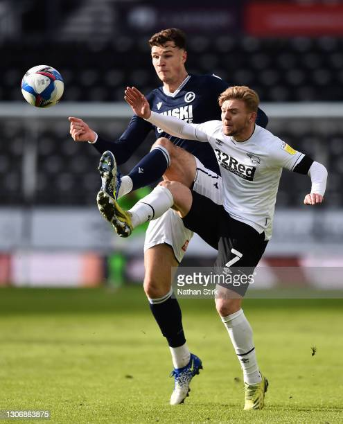 Kamil Jozwiak of Derby County battles for possession with Jake Cooper of Millwall FC during the Sky Bet Championship match between Derby County and...