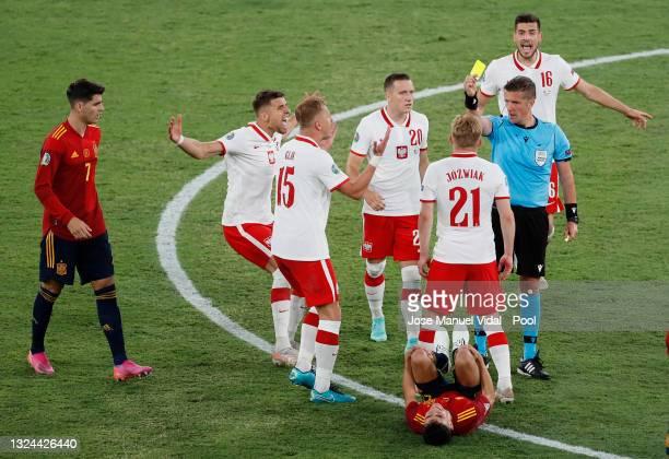 Kamil Jozwiak of Poland is shown a yellow card by Match Referee, Daniele Orsato as team mates Kamil Glik, Piotr Zielinski and Jakub Moder protest...