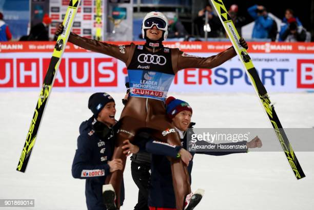 Kamil Stoch of Poland celebrate with his team mates after he wins the FIS Nordic World Cup Four Hills Tournament on January 6, 2018 in Bischofshofen,...