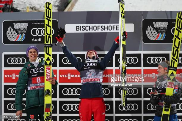 Kamil Stoch of Poland celebrates as he stands between Andreas Wellinger of Germany and AndersFannemel of Norway after winning all four jumps at the...