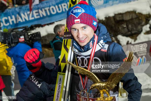 Kamil Stoch of Poland celebrates holding the trophy in his hand after his final jump at the 66th Four Hills Tournament in Bischofshofen Austria 6...
