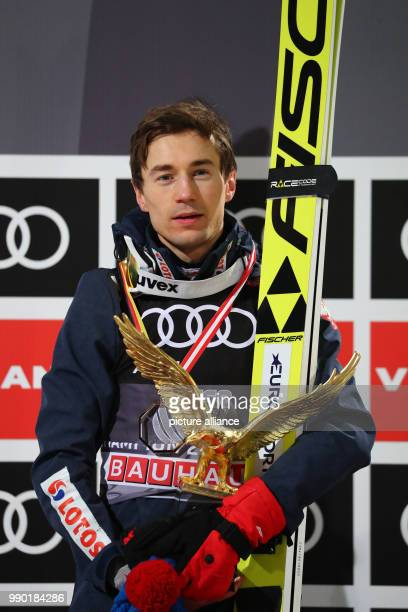 Kamil Stoch of Poland celebrates holding the trophy in his hand after his final jump at the Four Hills Tournament in Bischofshofen Austria 6 January...