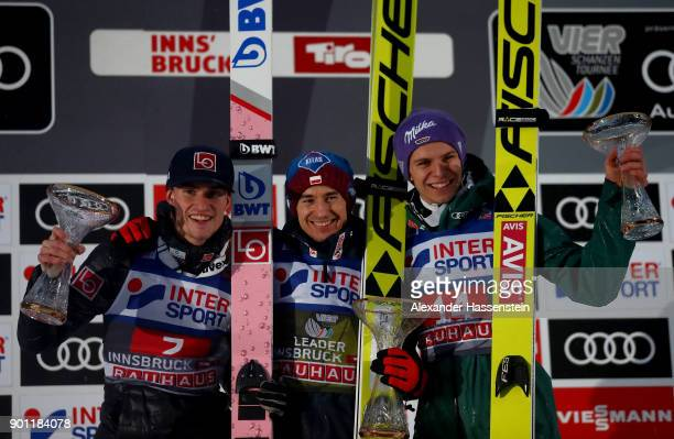 Kamil Stoch of Poland celebrates victory next to Daniel Andre Tande of Norway and Andreas Wellinger of Germany after the final round of the 65th Four...