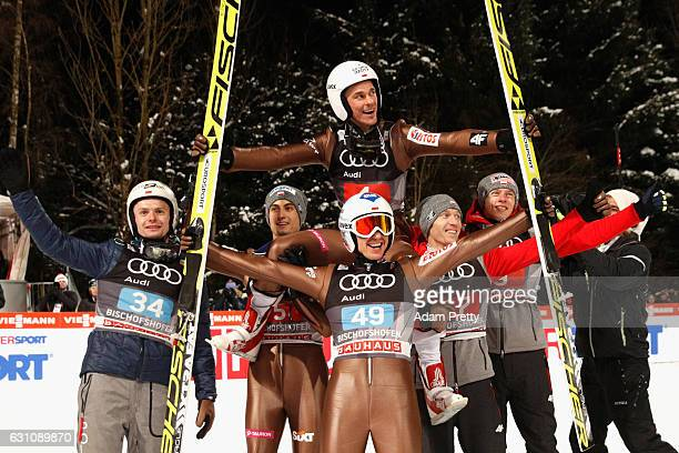Kamil Stoch of Poland celebrates victory with his team mate Piotr Zyla and others after the final round on Day 2 of the 65th Four Hills Tournament...