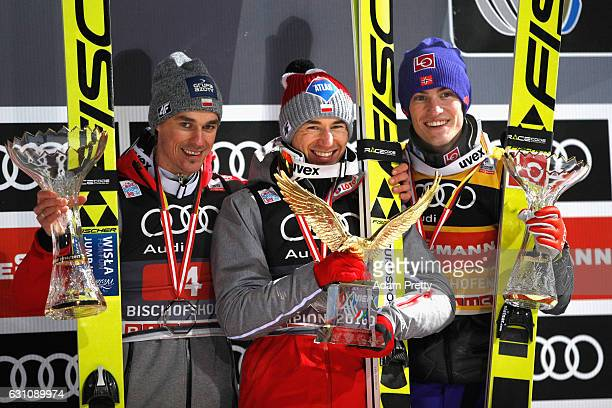 Kamil Stoch of Poland celebrates winning the 65th Four Hills Tournament ski jumping event with Daniel Andre Tande of Norway and Piotr Zyla of Poland...