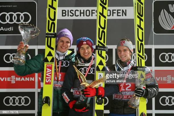 Kamil Stoch of Poland celebrates with Andreas Wellinger of Germany and AndersFannemel of Norway after winning all four jumps at the Four Hills...
