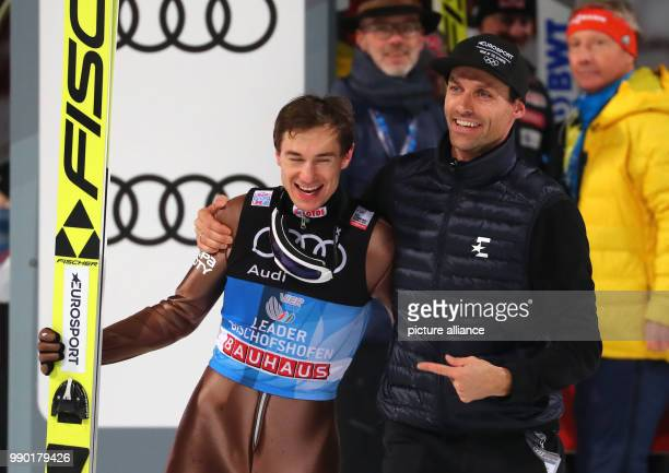 Kamil Stoch of Poland celebrates with Sven Hannawald after his jump in the second round at the Four Hills Tournament in Bischofshofen Austria 6...