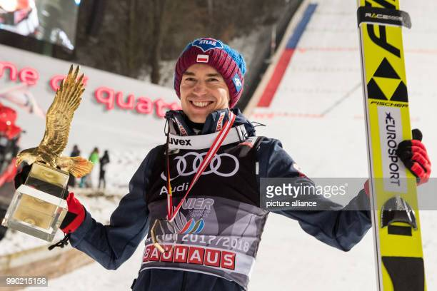 Kamil Stoch of Poland celebrates with the golden eagle trophy for the overall victory in the Four Hills Tournament in Bischofshofen Austria 6 January...