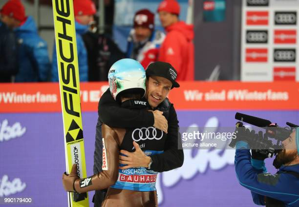Kamil Stoch of Poland embraces Sven Hannawald after his jump in the second round at the Four Hills Tournament in Bischofshofen Austria 6 January 2018...