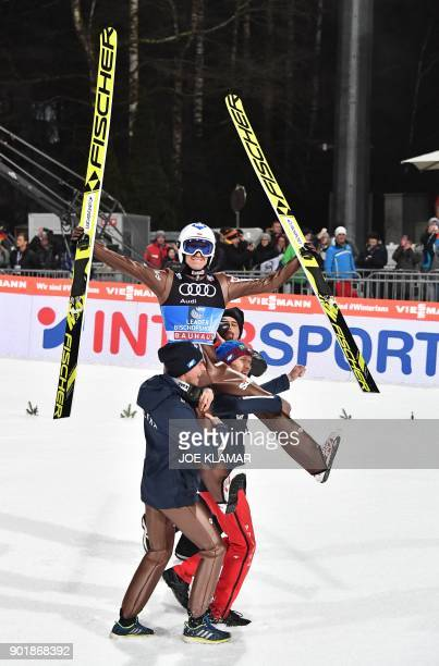 Kamil Stoch of Poland is carried on the shoulders of his teammates after winning the fourth and final stage of the Four-Hills Ski Jumping tournament...