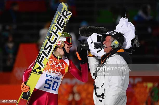 Kamil Stoch of Poland is congratulated by a cameraman after winning gold in the Men's Normal Hill Individual Final on day 2 of the Sochi 2014 Winter...
