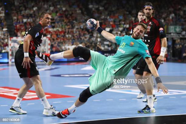 Kamil Syprzak of Barcelona eludes Momir Ilic and Laszlo Nagy of Veszprem during the VELUX EHF FINAL4 3rd place match between Telekom Veszprem and FC...