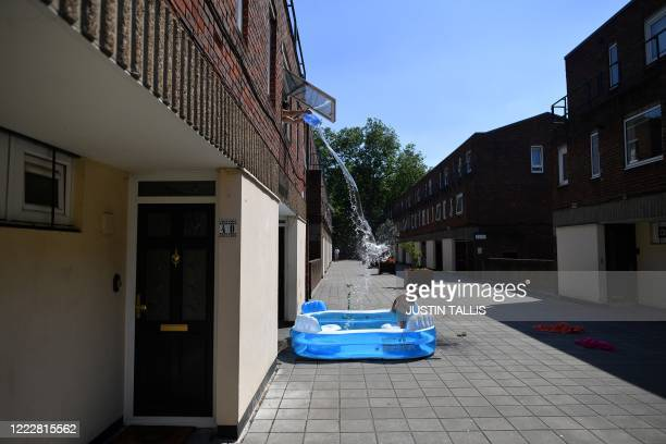 Kamila fills up a paddling pool by throwing water from an upstairs window over her son fiveyearold Luca as he stands in it to cool down in Hackney...