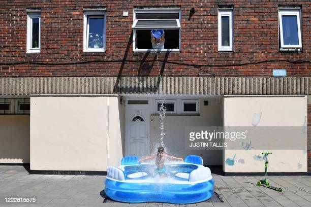 Kamila fills up a paddling pool by throwing water from an upstairs window over her son fiveyearold Luca as he stands in it in Hackney east London on...