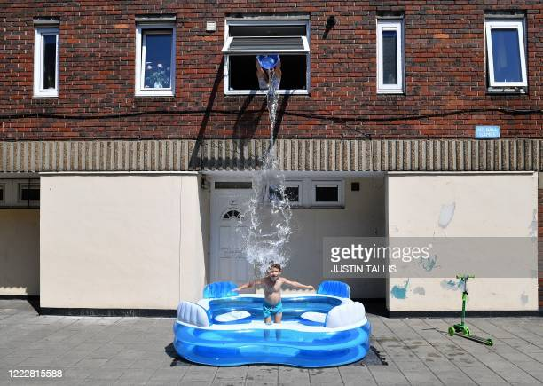 TOPSHOT Kamila fills up a paddling pool by throwing water from an upstairs window over her son fiveyearold Luca as he stands in it in Hackney east...