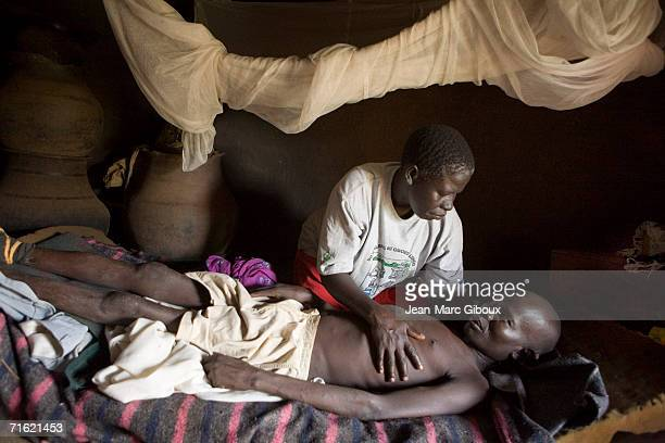 Kamila Shello looks after her 41 year old husband who is suffering from Aids inside their hut on June 17 2006 in Patongo IDP camp in Pader district...