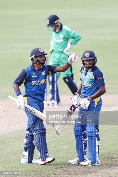 Kamindu Mendis of Sri Lanka celebrates scoring a half century with teammate Dhananjaya Lakshan during the ICC U19 Cricket World Cup match between Sri...