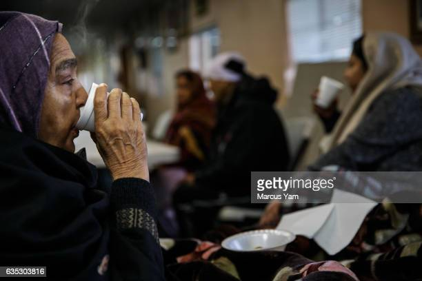 Kamlesh Nahar, left, and her daughter, Manita Sidhu, right, sip on chai tea for breakfast as they wake up from spending the night at the Shri Guru...