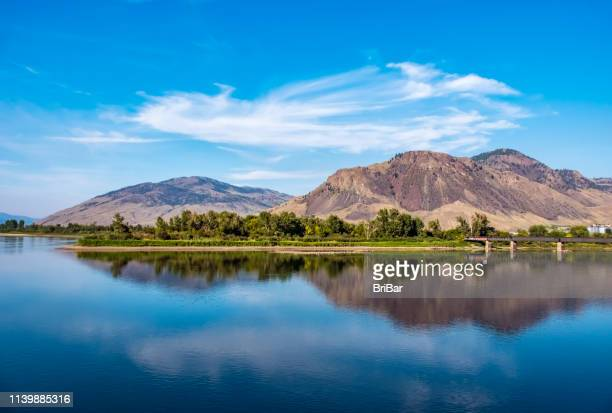 kamloops, bc - thomson river, mountain range and railway bridge - kamloops stock pictures, royalty-free photos & images