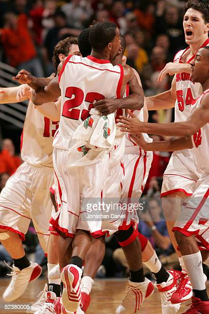 Kammron Taylor of the Wisconsin Badgers and his teammates including Mike Wilkinson swarm Alando Tucker after Tucker made a gamewinning 3pointer at...