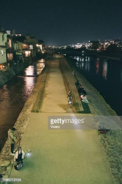 kamogawa (鴨川) riverside at night, kyoto, japan - vsojoy stock pictures, royalty-free photos & images