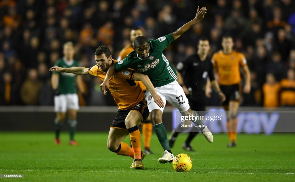 Kamohelo Mokotjo of Brentford is tackled by Leo Bonatini of Wolverhampton Wanderersduring the Sky Bet Championship match between Wolverhampton and Brentford at Molineux on January 2, 2018 in Wolverhampton, England.