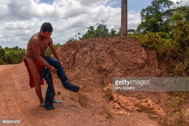 Kamon Waiapi puts on pants right before arriving at the city of Pedra Branca do Amapari in Amapa state in Brazil on October 15 2017 The Waiapi are...