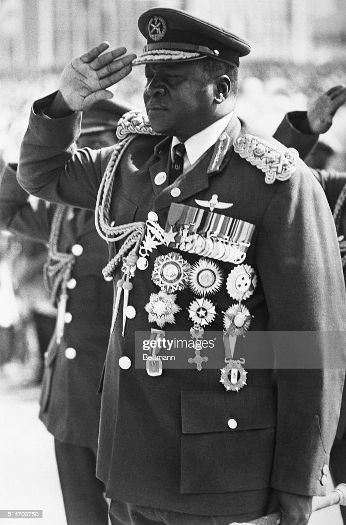 Prsident Idi Amin, in Air Force uniform bedecked with medals, takes the salute at a military march in the capital. Feb. 1975