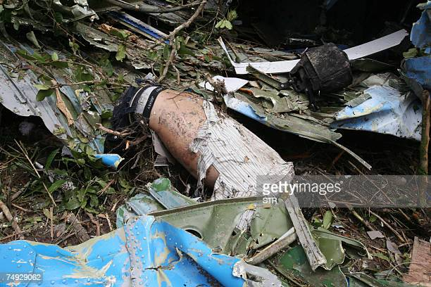 A body lies among debris sat the crash site of a Russianmade AN24 which disappeared after leaving the Angkor temple town of Siem Reap early 25 June...