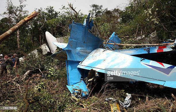Cambodian rescuers work at the crash site of a Russianmade AN24 which disappeared after leaving the Angkor temple town of Siem Reap early 25 June on...