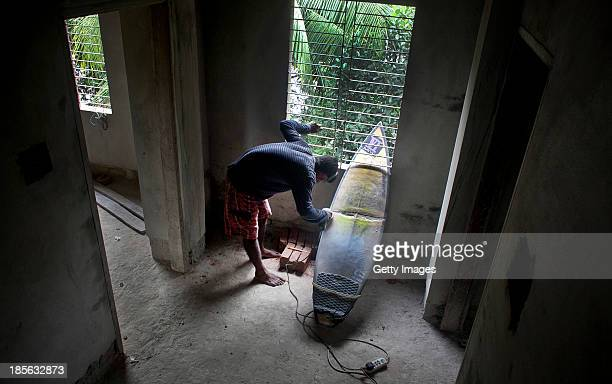 COX'S BAZAR BANGLADESH OCTOBER 23 Kamrul Hasan repairs his surfboard on October 23 2013 in Cox's Bazar Bangladesh Cox's Bazar is the world's longest...
