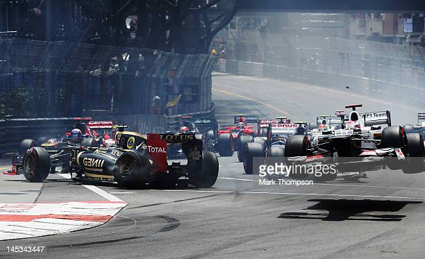 Kamui Kobayashi of Japan and Sauber F1 is launched into the air as he touches wheels with the spinning Romain Grosjean of France and Lotus at the...