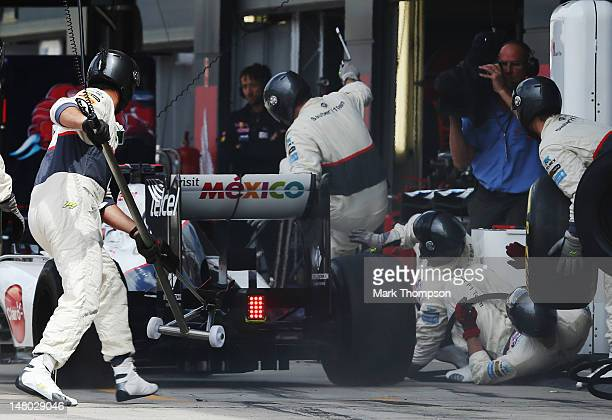 Kamui Kobayashi of Japan and Sauber F1 knocks over several members of his crew as he stops for a pitstop during the British Grand Prix at Silverstone...
