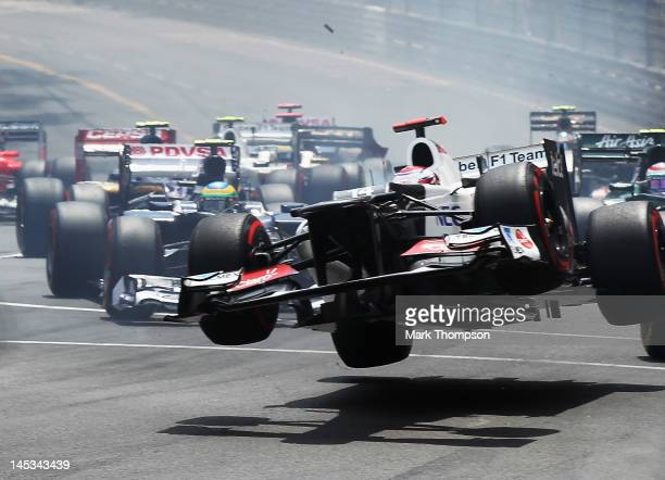Kamui Kobayashi of Japan and Sauber F1 touches wheels with the spinning Romain Grosjean of France and Lotus at the start of the Monaco Formula One...