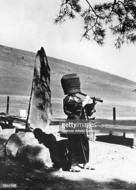 A KamuSo Buddhist monk wearing a basket over his head while playing sacred music on a bamboo flute