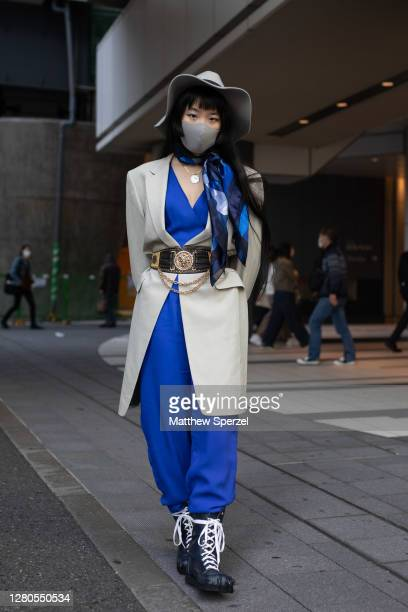 Kana is seen on the street wearing blue dress, taupe blazer, vintage belt, grey hat and face mask, blue silk scarf and navy leather claw boots during...