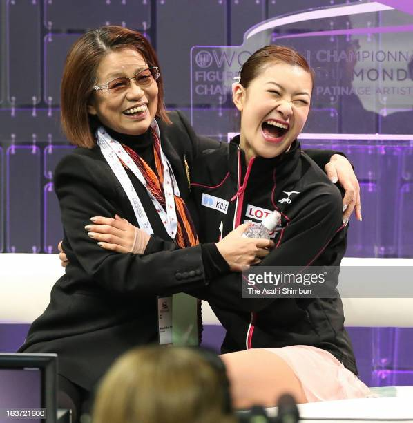 Kanako Murakami of Japan and coach Michiko Yamada react after her score was posted after the performance in the Ladies Short Program during the 2013...
