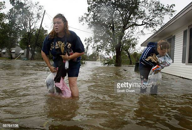 Kandy Huffman and her niece recover belongings that dropped in the water as they make their way through flooded streets to Huffman's home following...